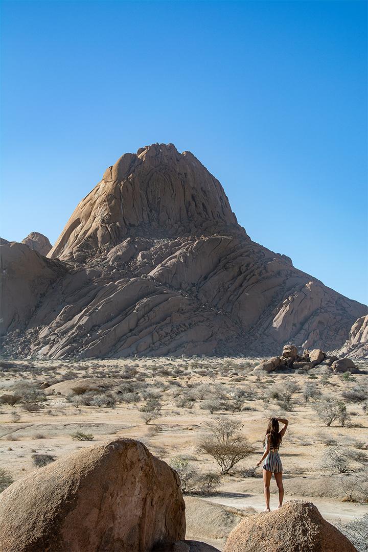 Femme en face d'énormes rochers à Spitzkoppe